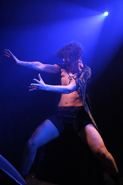 Chiyo a mixed race transgendered man stands definately with his legs apart and arms cast out to one side, like he is summoning something. He is wearing black studded shorts and a black shiny cape. His hair is black and tousled. He appears to be screaming. He is on stage, the light is a dramatic combination of blue and black.