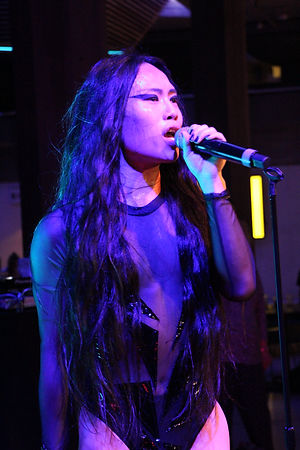 A close up of an asian performer singing into a microphone. Her black long hair is down. She has neatly applied blue eyeshadow painted in a delicate triangle shape. She is wearing a long sleeved tight fitting bcal top. Bluish white light hits her face. The backdrop is dark.