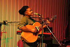 A black person holds an acoustic guitar and plays whilst singing into a microphone on a stand. Their long black braids are pulled into a large loose bun, their eyes are closed in concentration. They are wearing a light green jumper. There is a keyboard in the background.
