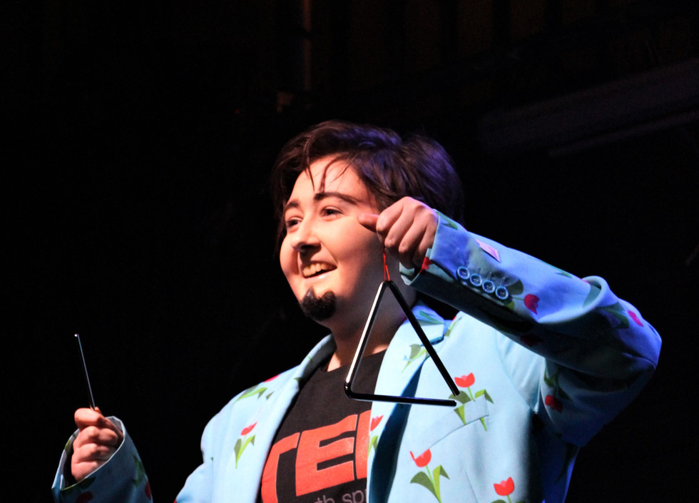 Indie, a drag king, plays a triangle. He is wearing matching blue jacket and trousers with a flower print, and a TED shirt.