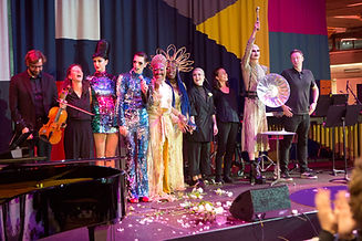 A group of nine people stand on a stage accepting applause. They are all smiling and appear happy, with arms raised. Some are in drag, some are wearing black. A short white woman holds a violin.They are flanked by a piano and drum kit. White roses are scattered on the stage in front of then, and a small speaker faces them on the ground.