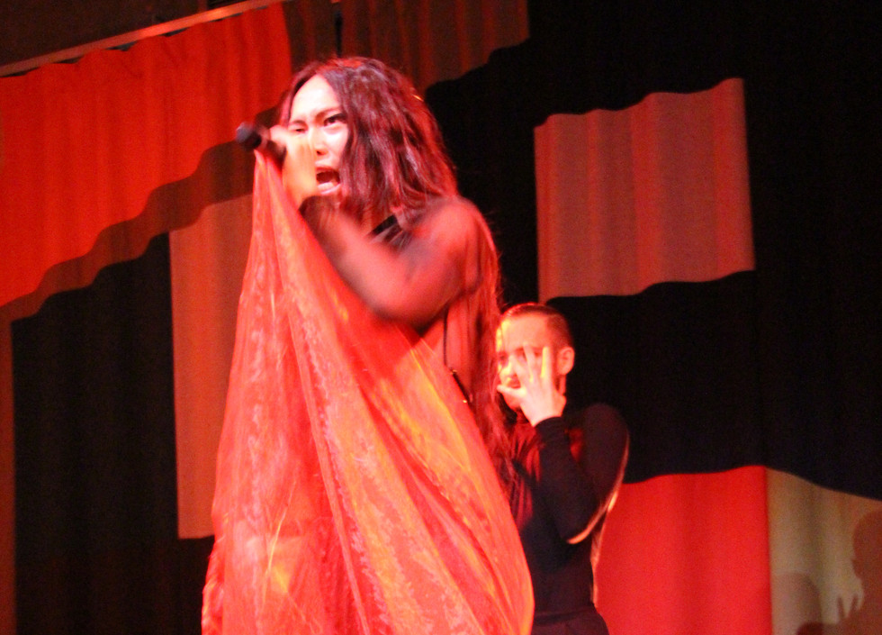 Le Fil, a British-Chinese man wearing a black dress and draped in red fabric sings