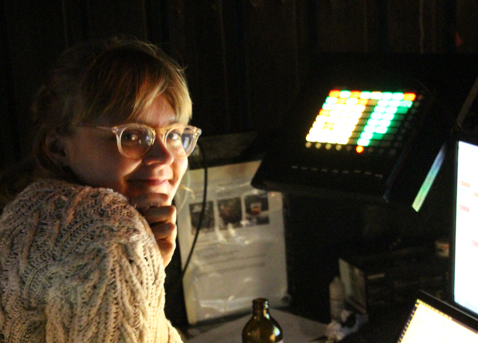 Sorcha, wearing a white knitted sweater and grey sweatpants, sits in front of a  laptop, smiling at the camera.