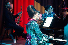 In the foreground is a woman seated at a grand piano, singing into a microphone whilst playing. She has a huge dark brown beehive hairstyle and wears a very glittery blue and purple long sleeved dress. In the background another performer in a similar outfit rests on the piano. On the left two musicians dressed in black are paused, watching the pianist.