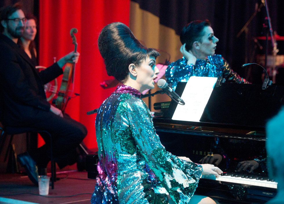 Maurice, a white woman with a black beehive and blue glittery dress plays a piano and sing. Behind her, to her left, sit a violinist and french horn player. Bourgeois, a white man, rests on the piano.