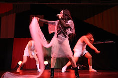 Le Fil, an asian performer stands confidently on centre stage, with legs apart and arms raised, singing into a microphone, their head turned to the left. They are wearing a black bodysuit with a loose fitting white floaty gown with a train, which they hold up in their right hand. In the background are two white, male dancers wearing white vests, shorts, trainers and socks.