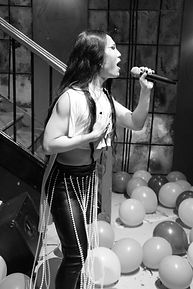 A black and white image of Le Fil an asian performer signing into a microphone on a stand. The person is sideways on to the camera. They have long dark hair and are wearing a white sleeveless top. In the background is the bannister of a staircase, cutting diagonally through the background. The wall behind is tiled.