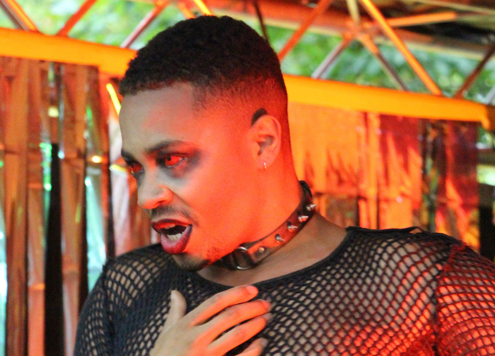 Rhys, a black man wearing a black mesh shirt and studded choker, holds one hand to his throat. He is wearing red eye contacts.