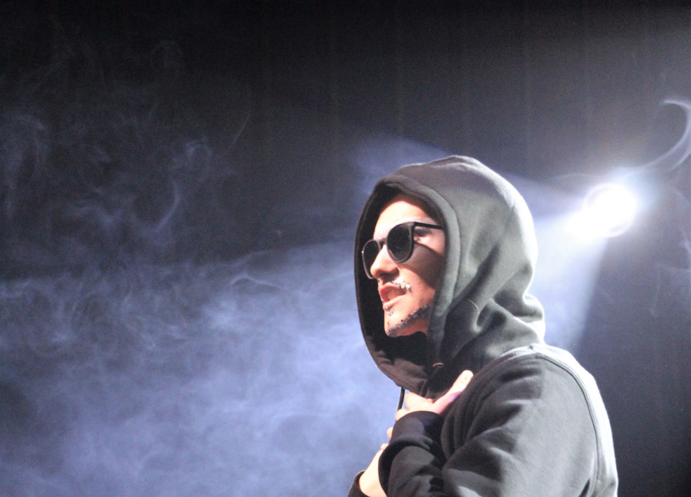 Silver, a drag king, stands wearing a black hoody and sunglasses.