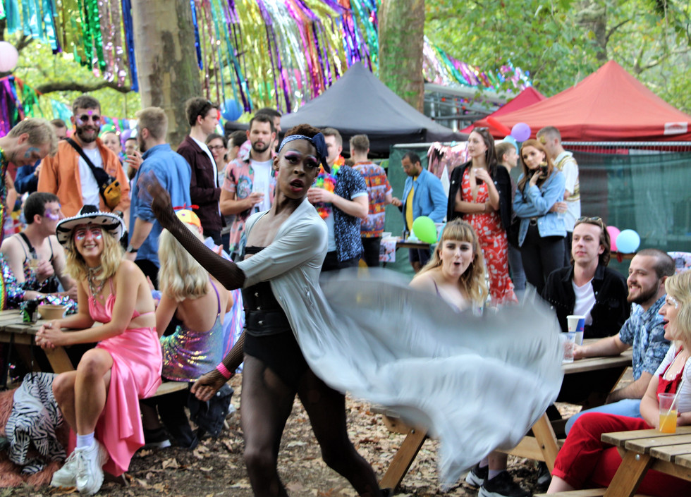 Shakona, a black drag queen wearing a black corset, spins her long slip around her as the audience, sitting on picnic benches, watches on.