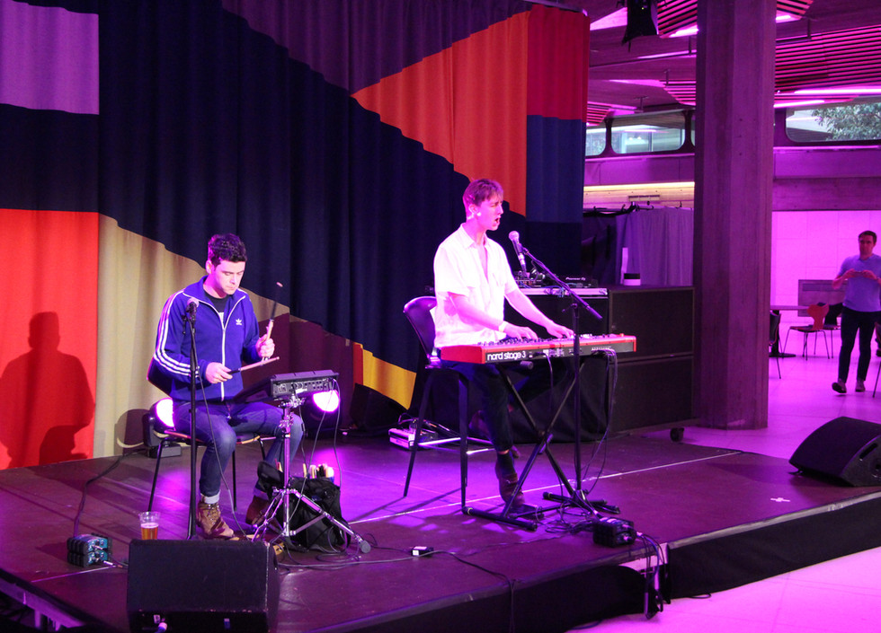 A white man in a blue tracksuit shirt plays the drum pad while Vaughan Music, a white man in a white shirt plays the keyboard and sings
