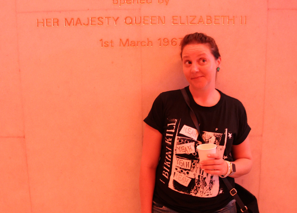 A white woman stands by the wall holding a drink