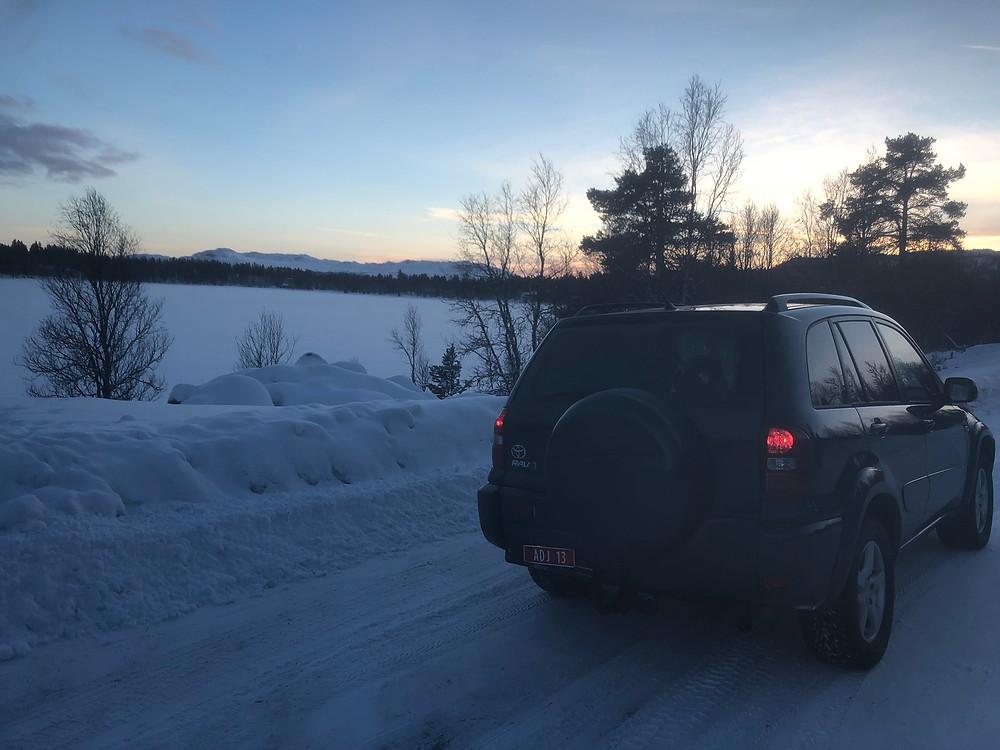 Bil står stille på Tunhovd, hvitkledd innsjø, hvitkledde snaufjell, svart bil. Solnedgangen har akkurat glidd forbi.