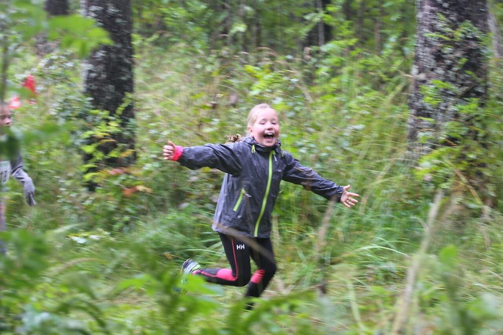 Et jublende barn løper i skogen