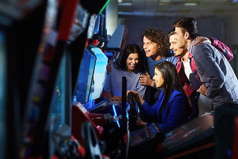 A group of friends playing arcade machin