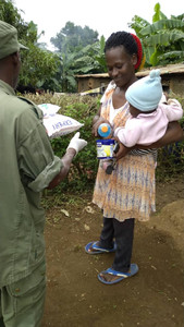 A member of the Uganda Army assist our relief programme by giving out food to a mother and baby