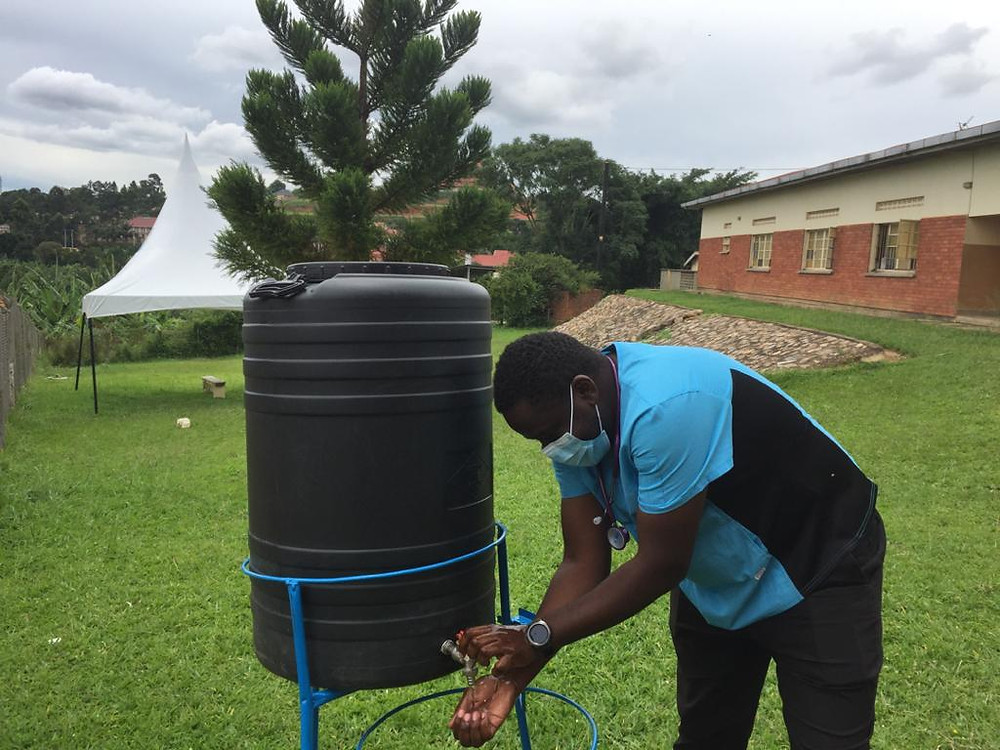 A doctor from Masaka referral hospital demonstrates the new hand washing facilities to help protect from Coronavirus