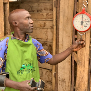 One of Community Recycle Managers with the scales that weigh people plastic waste in exchange for cash