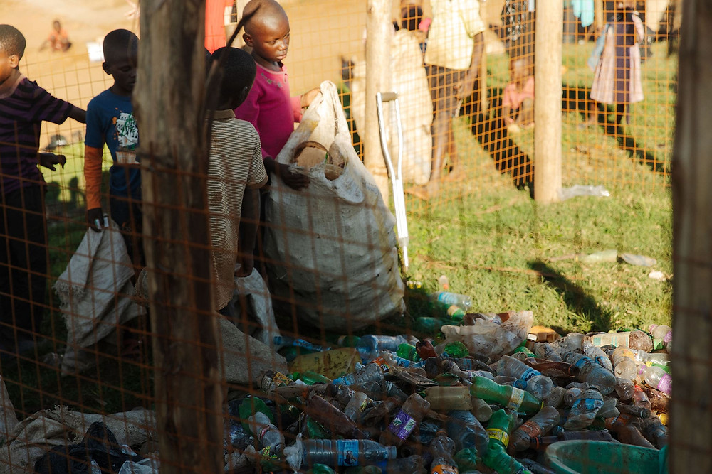 Children in Uganda collecting plastic waste in bags which can be exchanged for cash
