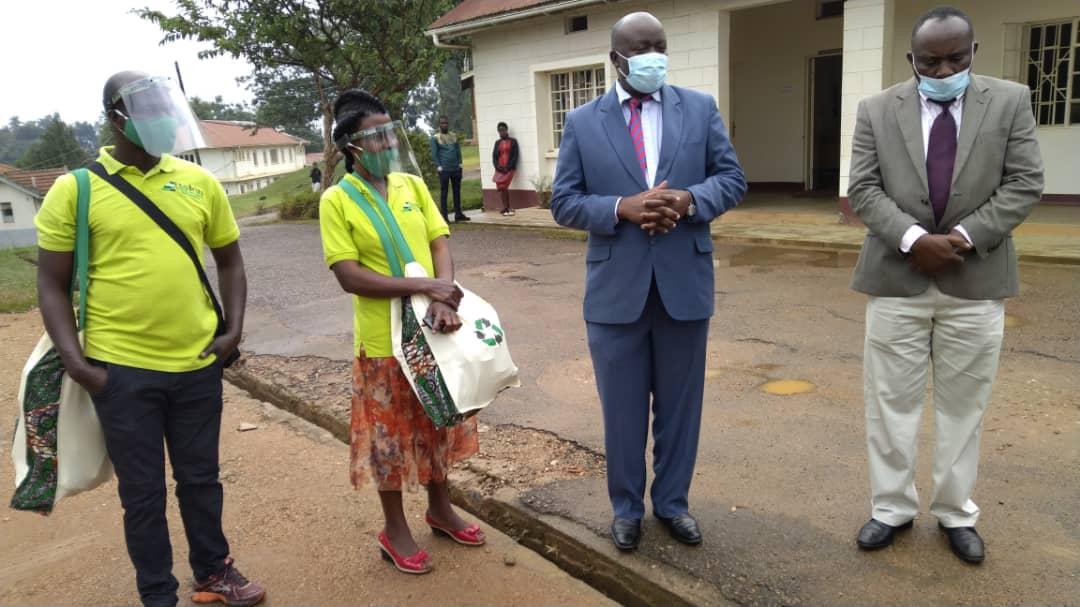 Regina Finances Officer with local officials presenting COVID-19 plastic face shields to Masaka Referral Hospital