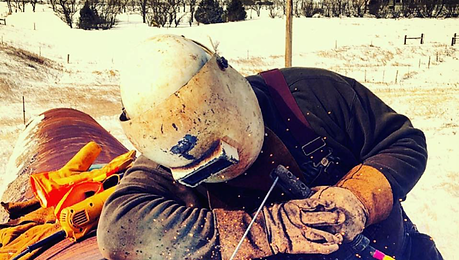 Image of a tired welder fully suited up