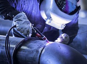 Worker welding metal piping using TIG