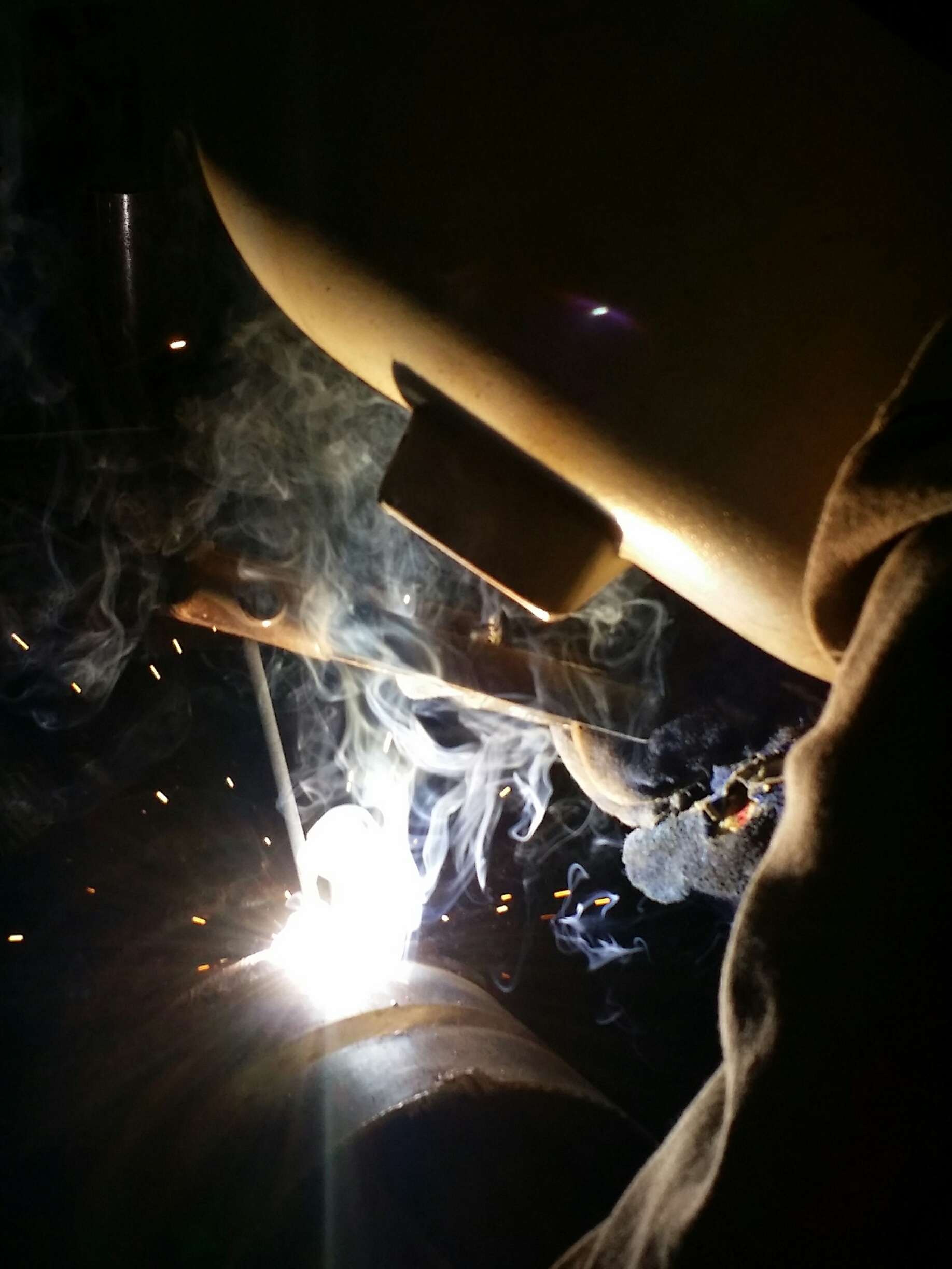 Image of a welder working on piping fixtures