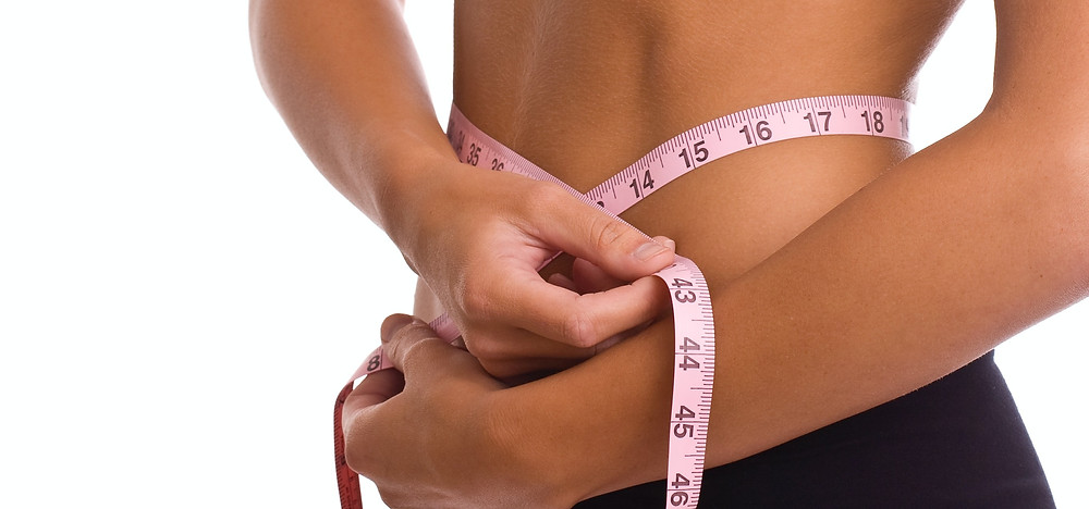 Woman on a diet measuring her waist with roll of tape.