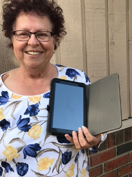 Ginette with her new TELUS tablet - Let us know if you need either a tablet or laptop to get connected.