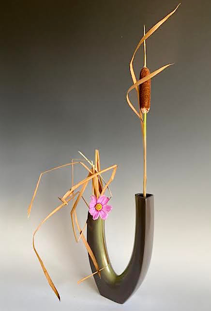 Ikebana with contemporary vase cattail and wild cosmos.