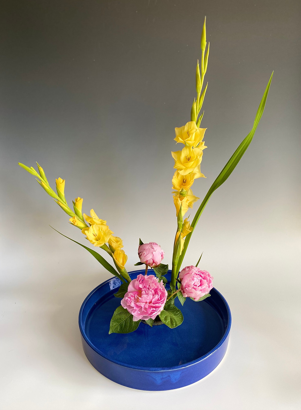 Basic moribana style ikebana with gladioli and peony.
