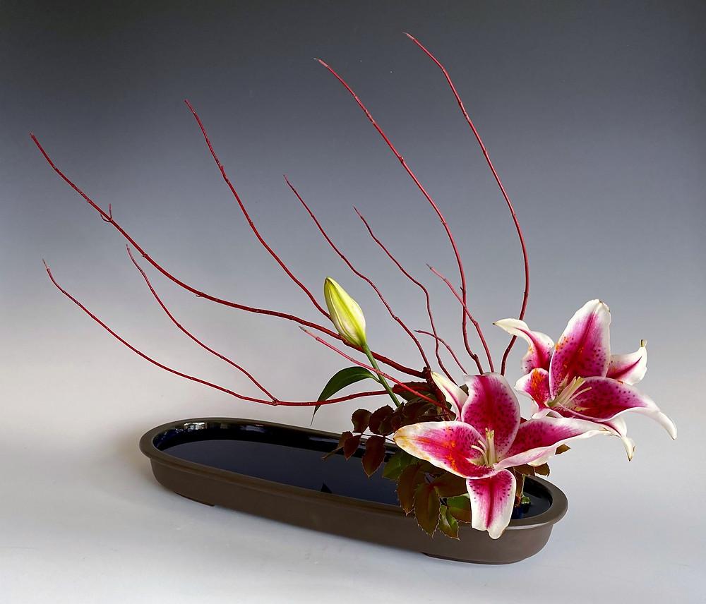 Japanese ikebana with dogwood and Stargazer lily in Ohara vase.