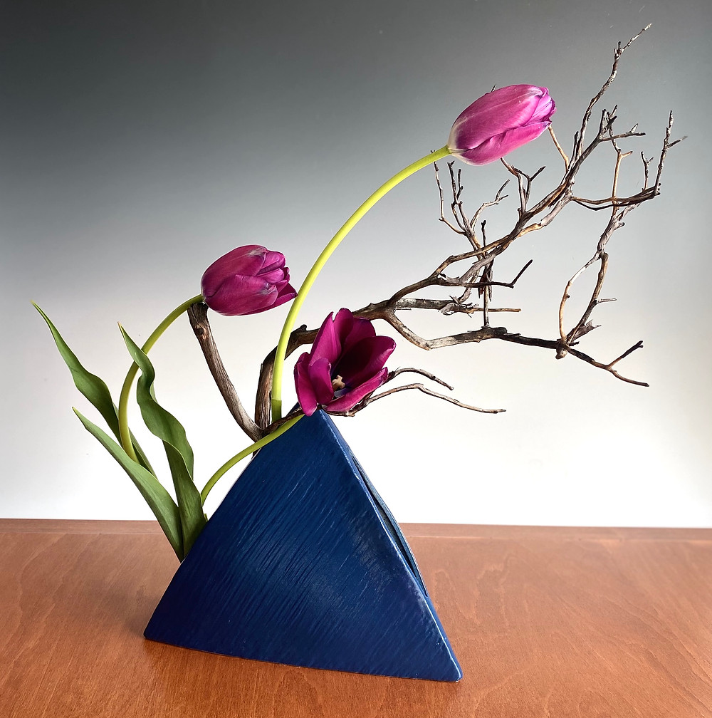 Japanese ikebana with tulip and manzanita in pyramid or triangle vase.