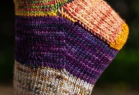 Zoom sur le gousset violet d'une chaussette tricotée à la main. Le gousset permet de créer de la matière pour couvrir le côté du talon.