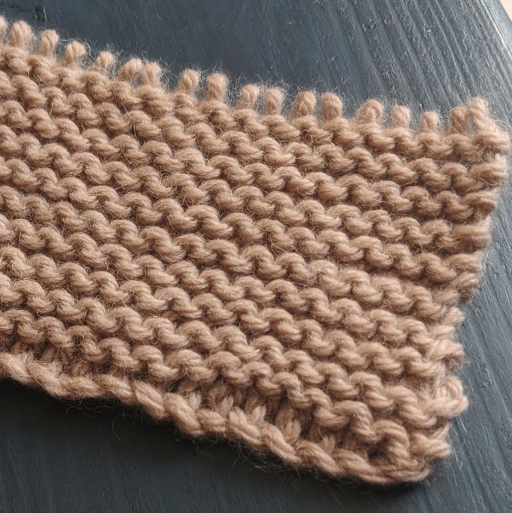 Photo d'un échantillon au point mousse, tricot texturé de creux (cachés) par les crêtes.