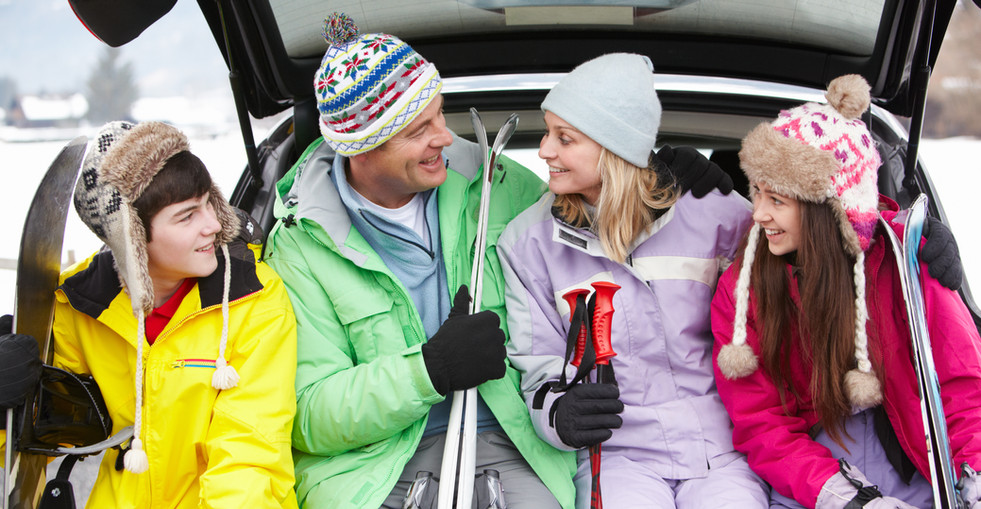 Teenage Family Sitting In Boot Of Car Wi