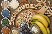 TN Scientific The Hangover Pill Ingredient Research woden blocks spelling out Magnesum surround by foods that contain magnesium on the wood table an in bowls bananas chocolate beans nuts peanuts