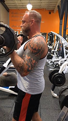 MuscleMakerSue training client doing bicep bar curls.