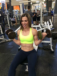 MuscleMakerSue training client doing seated bicep curls.