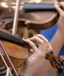 Viulunsoiton opiskelijoiden kädet viulun otelaudalla.