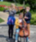 Nuorten musiikoiden trio soittaa ulkona.  Triossa mukana fagotti, huilu ja sello.