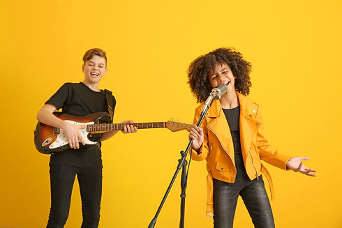 Teenage musicians playing against color background.jpg