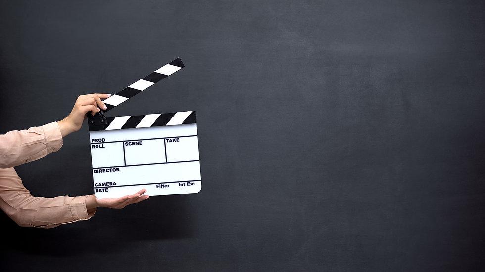 Female hands using clapperboard against black background, shooting movies.jpg
