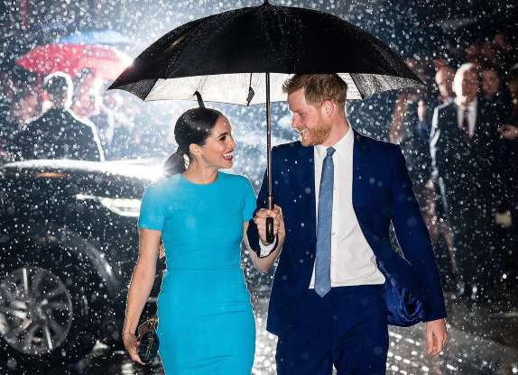 Harry and Meghan under an umbrella with flashlights