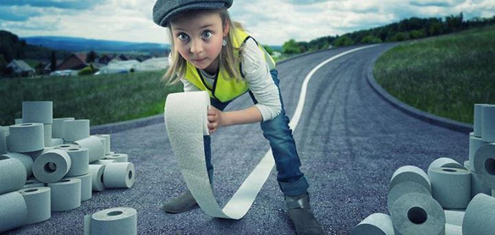 Child using toilet paper to paint white stripe in road