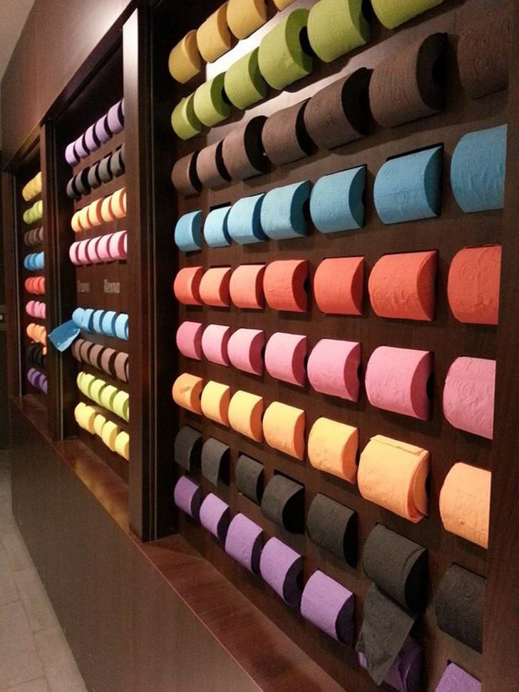 A wall of colored toilet paper rolls in a Paris shop