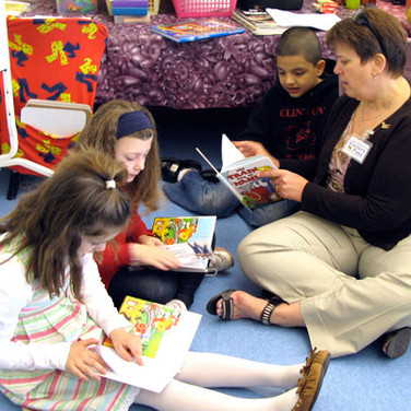 Reading books to first graders at March Elementary School