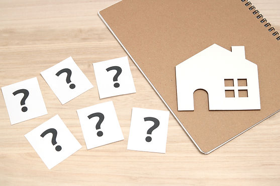 Miniature house and many question marks on white papers.  _House with question marks. Real