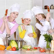 Three cheerful girls preparing food in t