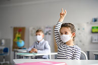 Child with face mask back at school afte